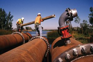 Workers carrying pipe